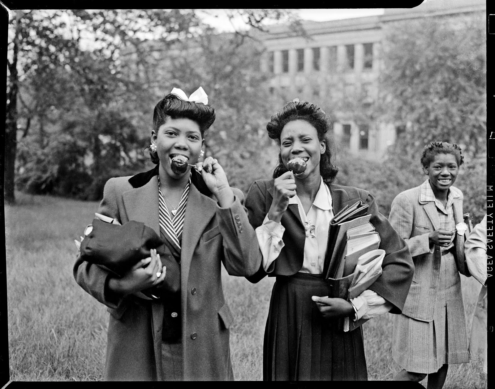 "Two young women eating caramel apples, c. 1940–1945. Photograph by Charles ""Teenie"" Harris courtesy of Eyes on Pittsburgh and the Carnegie Museum of Art."